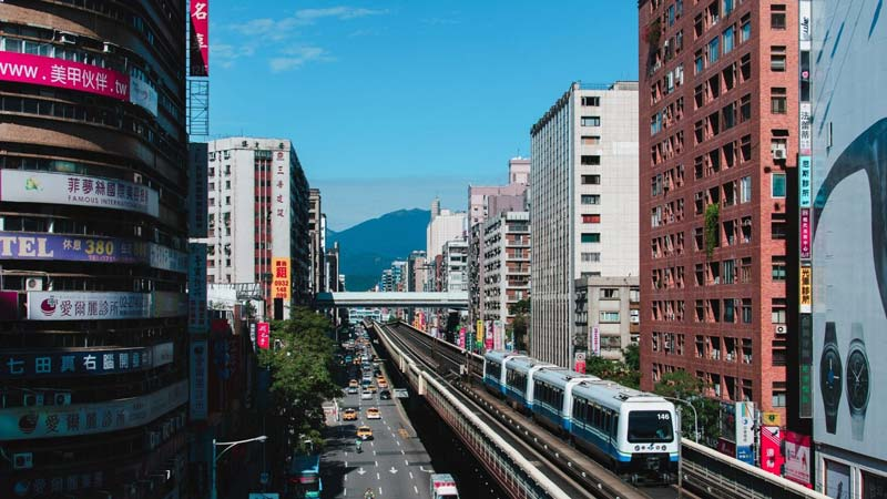 A train is driving on a railway between high buildings in Taiwan.