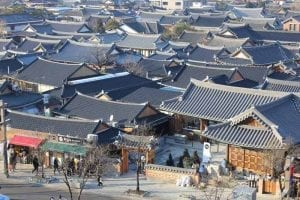 Low rise buildings in the Hanok style in Korea. People are mingling in front of the buildings