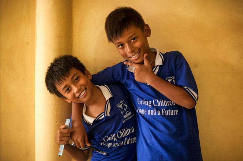 Two kids dressed in blue smiling at the camera