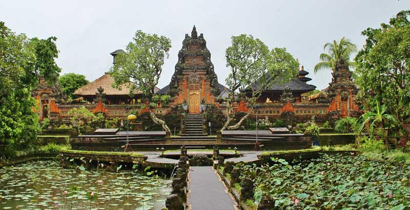 A pathway lined by water leads to a square, behind which is a temple, in Ubud, Bali