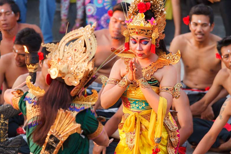 A woman in a yellow traditional dress and headdress bows her head in prayer