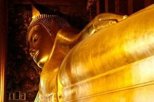 Huge golden statue of a humanoid buddha figure lying on its side in Thailand