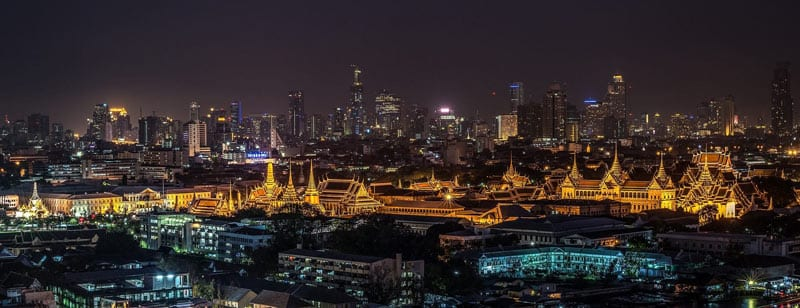 A dark city in Bangkok sees the grand palace, an ancient set of buildings, lit up brightly