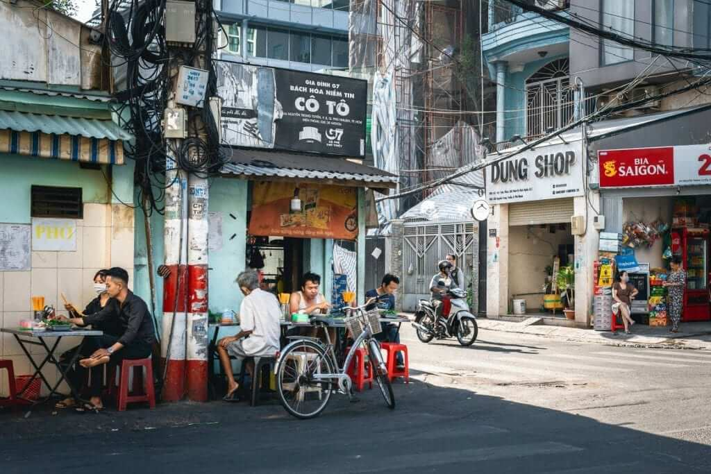 Local Vietnamese people sitting and eating outside a street food restaurant.