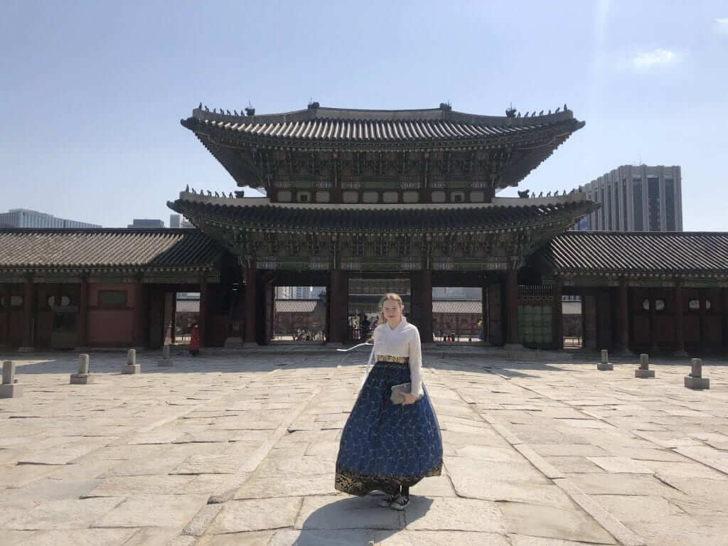 a girl is standing in front of a temple in Seoul while wearing a traditional dress