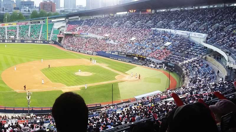 Thousands of people at a stadium in Korea enjoying a baseball game