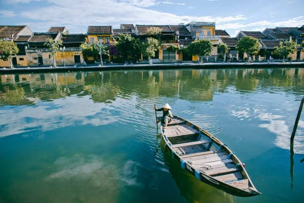 A person sitting on a boat by the river in Vietnam.