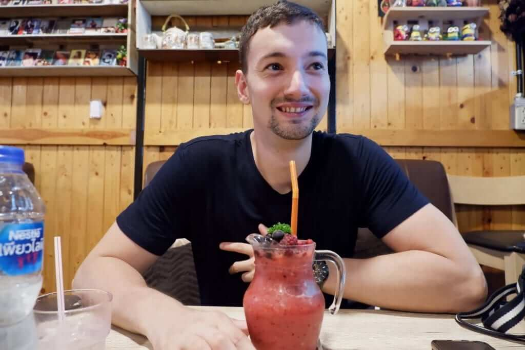 man is smiling while having a strawberry smoothie in fron of him