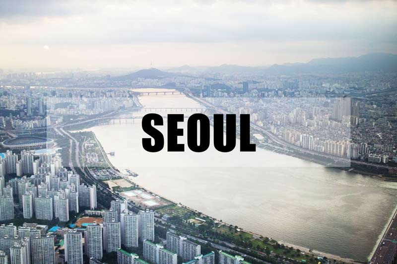 "The city of Seoul is the backdrop and the text ""Seoul"" appears in the center in bold, black letters"