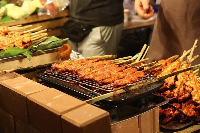 Skewers of meat on a roadside stall in Thailand being grilled and waiting to be grilled