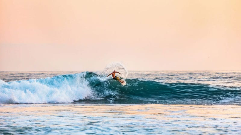 Surfer on the top of a wave in Bali during sunset