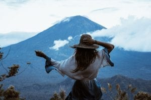 girl holding her hat while watching the view of a mountain in Bali