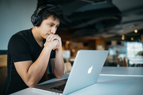 a guy in black shirt wearing headphones is looking at a laptop