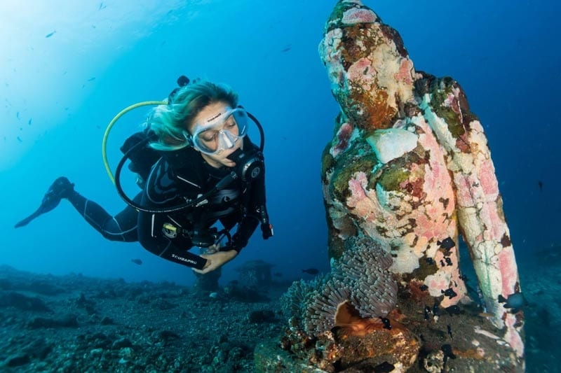 A woman in scuba diving gear is examining an underwater pillar