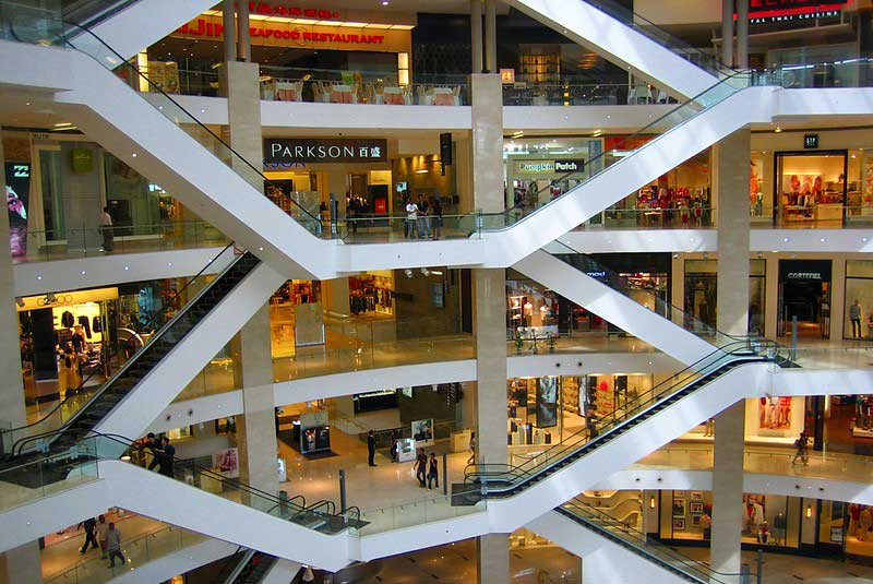 A large open atrium in a shopping mall, multiple stores are visible on numerous floors