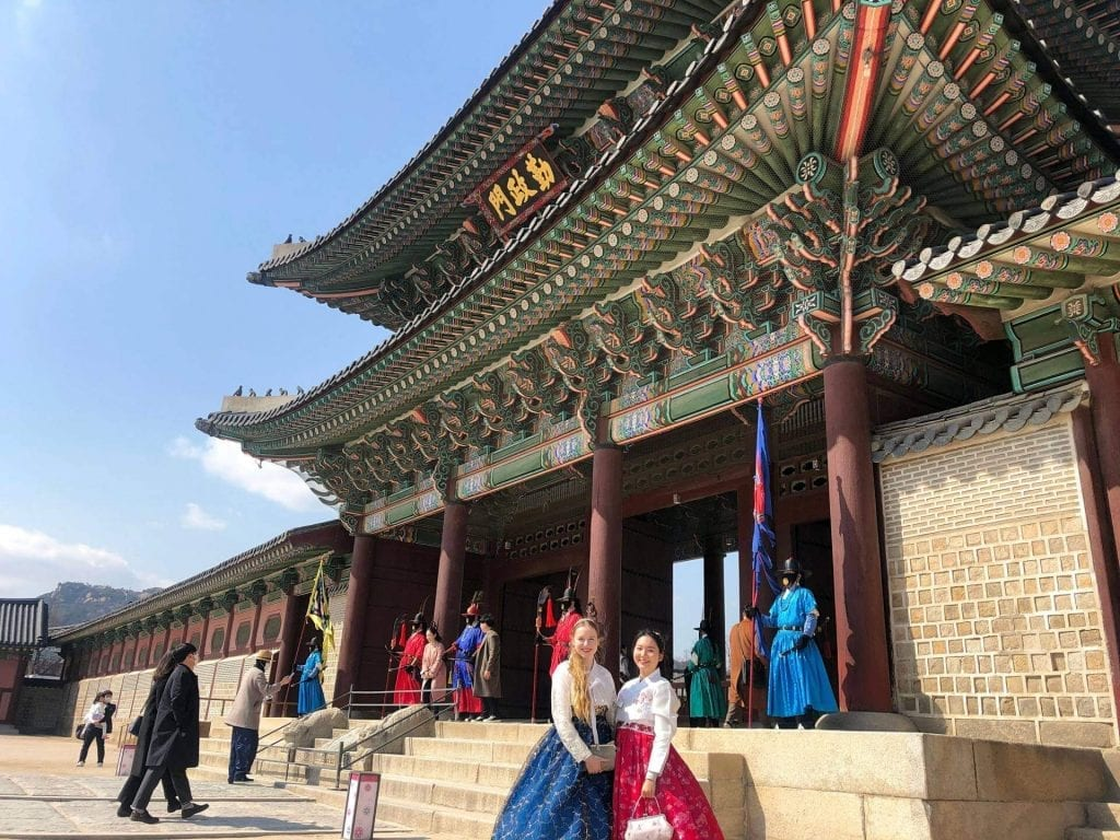 two woman wearing traditonal south korean outfits are standing in front of a temple in seoul