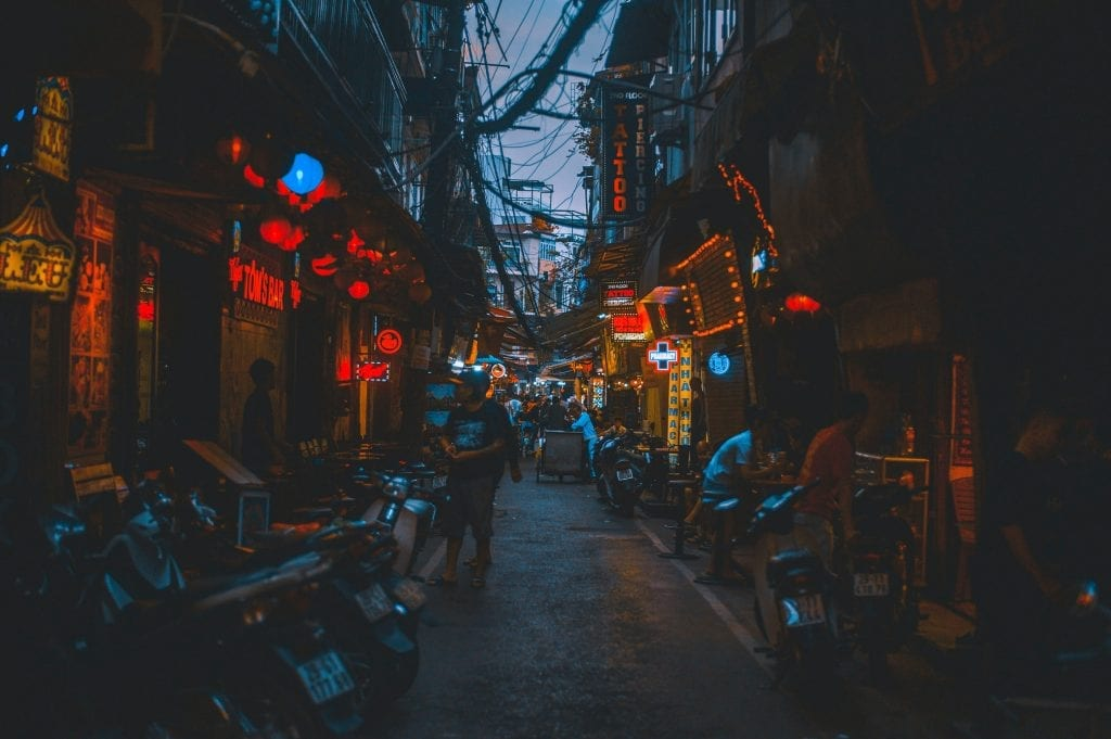 People along a narrow alley in Vietnam at night.