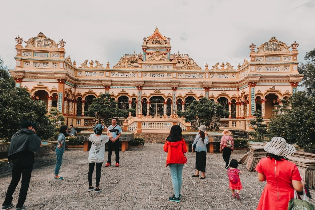 People standing near a temple in Vietnam.
