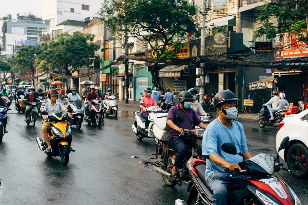 People riding on motorcycles on a busy road in Vietnam.