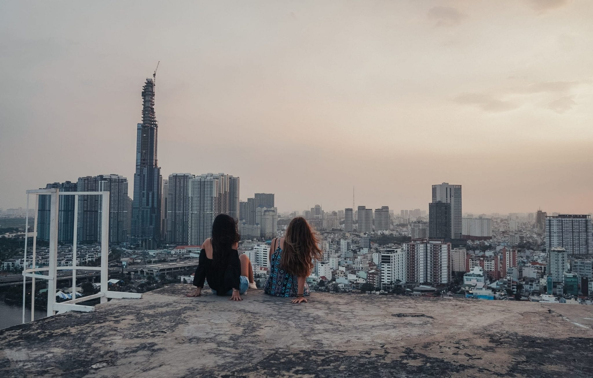 Two girls watching the inner city of Ho Chi Minh from a roof top