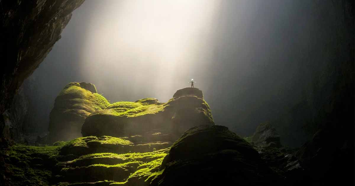 man is standing on a lush green hill inside of a cave in vietnam