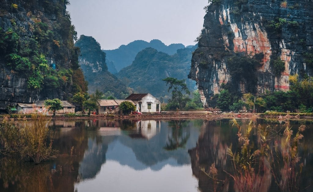 A white house in between two big cliffs in a tropical landscape in Vietnam by the water