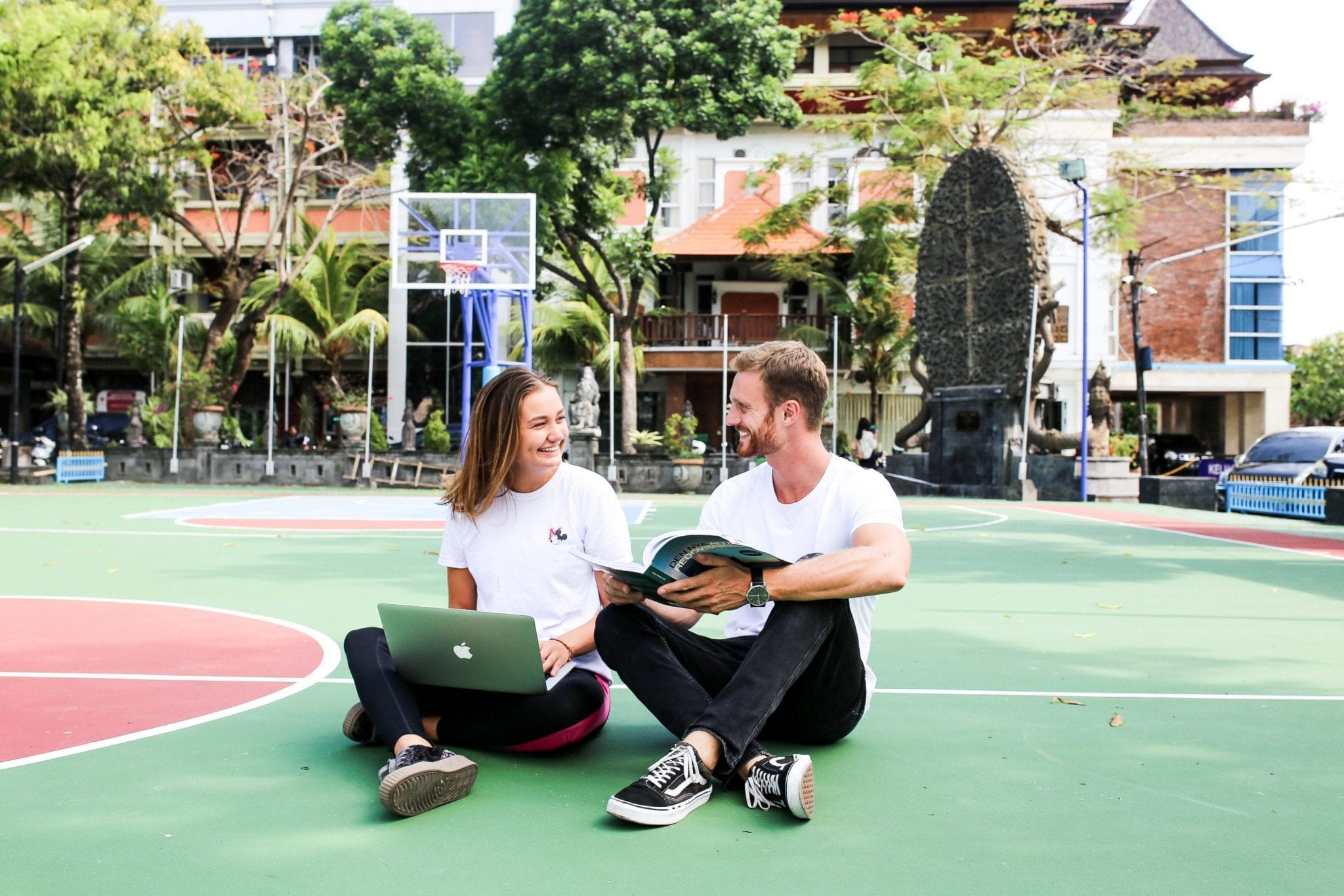 a man and a girl is sitting on the ground holding a book and a laptop in Bali
