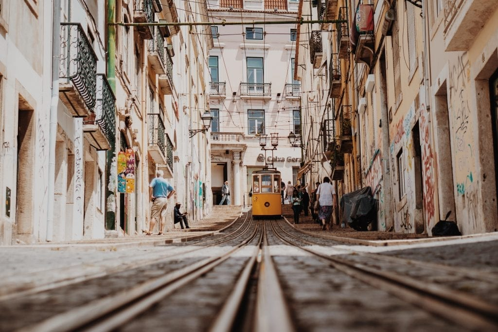 a yellow tram is going through the city of Lisbon in Portugal