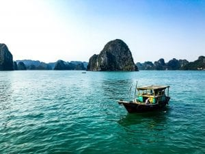 traditional vietnamese boat is floating in the water with islands in the background