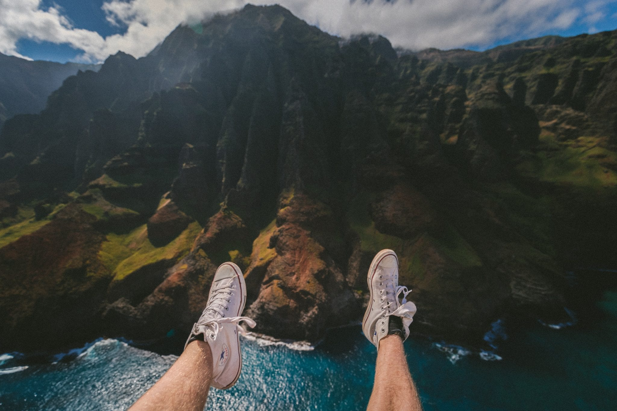 sitting on the cliff with wearing white converse shoes