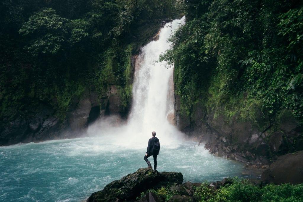 men waterfall blue pool green rain forest