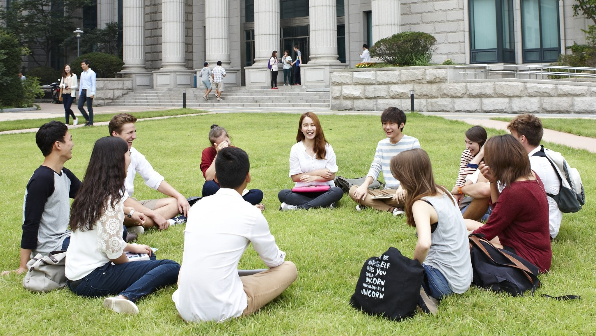 students sitting by HUFS university in South Korea